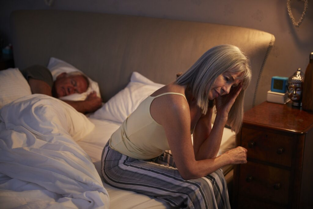 Worried Senior Woman In Bed At Night Suffering With Insomnia